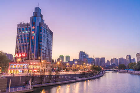 TIANJIN, CHINA - NOVEMBER 18: Evening view of riverside city buildings in the downtown area on November 18, 2019 in Tianjin Stock Photo - 147381428