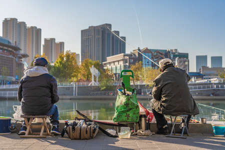 TIANJIN, CHINA - NOVEMBER 19: Chinese fishermen fishing on the Hai River in the downtown area on November 19, 2019 in Tianjin Stock Photo - 147381435