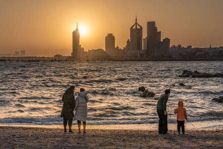 QINGDAO, CHINA - NOVEMBER 14: This is a scenic view of a beach with people watching the sunset on November 14, 2019 in Qingdao