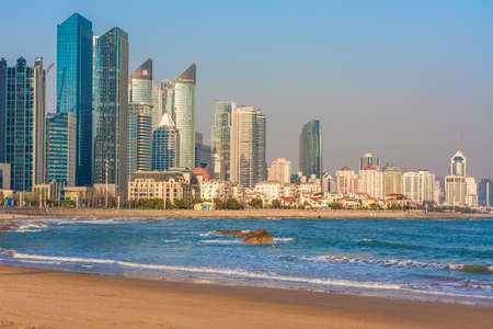 QINGDAO, CHINA - NOVEMBER 15: View of waterfront city buildings from a quiet beach on November 15, 2019 in Qingdao