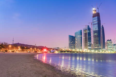 QINGDAO, CHINA - NOVEMBER 15: This is a night view of a beach with high rise city buildings in the distance on November 15, 2019 in Qingdao