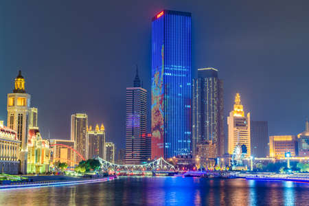 TIANJIN, CHINA - NOVEMBER 16: Night view of downtown city skyscrapers along the River Hai on November 16, 2019 in Tianjin