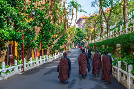 KAOHSIUNG, TAIWAN - NOVEMBER 24: Monks walking a treelined path in the Fo Guang Shan monastery on November 24, 2016 in Kaohsiung Editorial