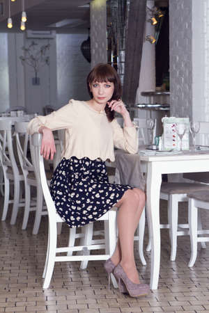 charmingly: Yong woman in a elegant dress sitting at the table