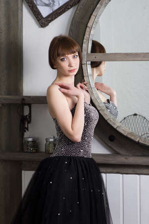 charmingly: Beautiful young woman in the black dress staying at the mirror Stock Photo