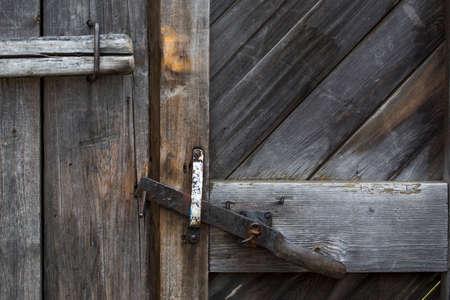 door bolt: The door bolt closes an old wooden door. Textural wooden background