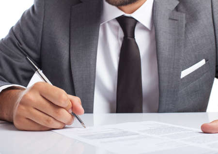 business man singing a contract on his desk on white background