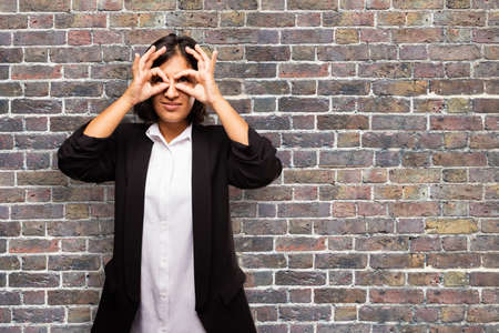latin business woman doing glasses gesture Stock Photo