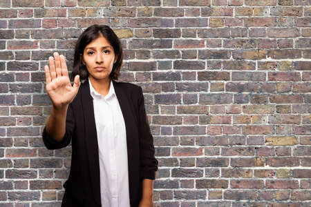 provoked: latin business woman doing stop gesture