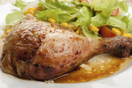 close-up of a roast chicken leg with mixed salad and sauce in a dish photo