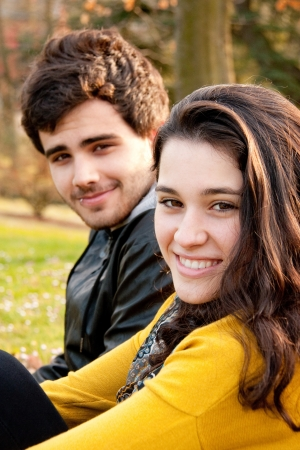 a beautiful girl with a handsome boy sitting in a park in springtime smiling