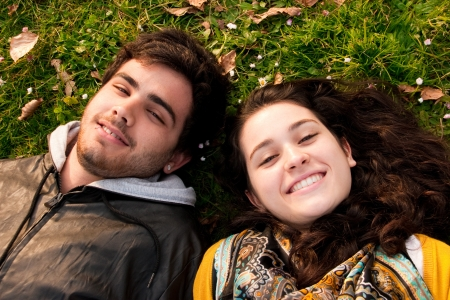 attractive couple of teenagers lying in the grass smiling photo