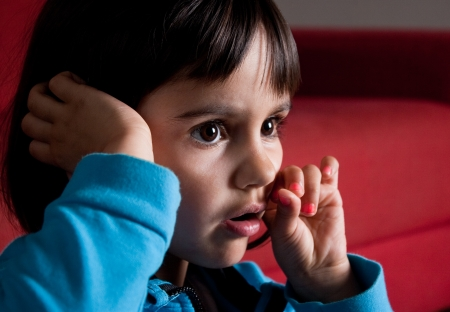 little girl concentrated watching tv alone with the eyes and mouth opened Stock Photo