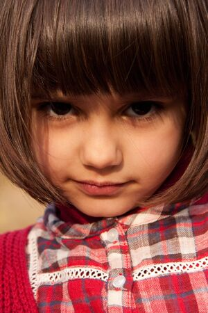 close-up of a beautiful little girl dressed in red with black big eyes and long fringe Stock Photo - 14329296