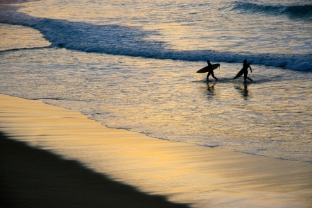 san sebastian: surfers out of the water at sunset in San Sebastian, Basque Country