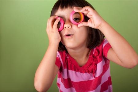 funny little girl pretending she wears eyeglasses