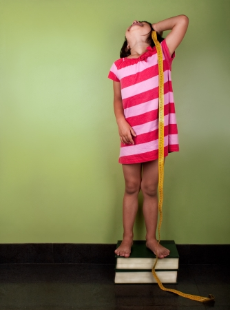 a funny little girl measuring herself with a yelow meter