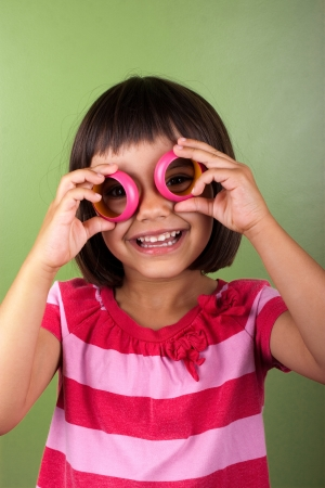 Funny girl making eyeglasses with napkin rings Stock Photo