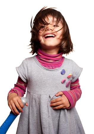 een mooi klein meisje zingen met een stuk speelgoed microfoon met verwarde haren Stockfoto
