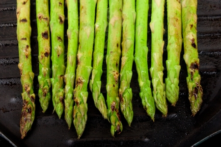 a handful of green asparagus cooking and steaming  on grill plate photo