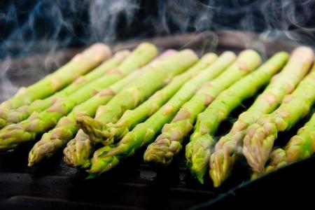 esparragos: un puñado de espárragos verdes cocinar y cocer al vapor en la placa de la parrilla