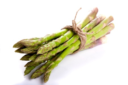 Isolated and lying bunch of asparagus tied with a string in a loop  Refection in the ground