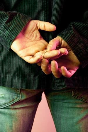 Man with hands behind his back, taking off his golden  wedding ring in a nightclub Imagens