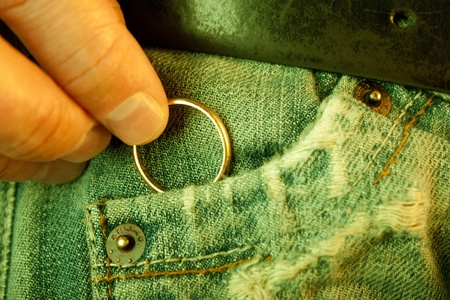 Concept of infidelity or asking in mariage  Closeup of a man�s hand put in or taking out a wedding ring in jeans pocket