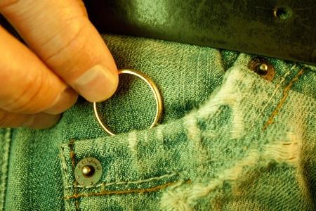 El concepto de infidelidad o preguntar en primer plano mariage de una mano sirve poner o sacar un anillo de bodas en el bolsillo de los pantalones vaqueros