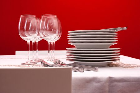 restaurant tables: Setting the table with wine glasses, dishes, napkins, forks, spoons and knives over a embroidered linen tablecloth. Red background.