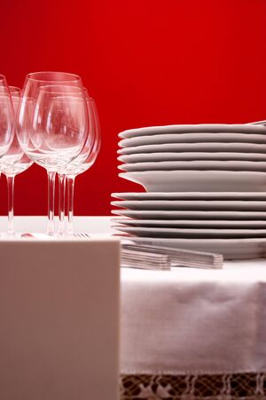 Setting the table with wine glasses, dishes, napkins, forks, spoons and knives over a embroidered linen tablecloth. Red background.