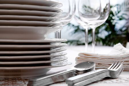 Setting the table with wine glasses, dishes, napkins, forks and spoons over a embroidered linen tablecloth. Window at the background.