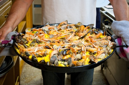 Carrying a freshly made seafood paella cooked in a basque gastronomic society in San Sebastian Stock Photo