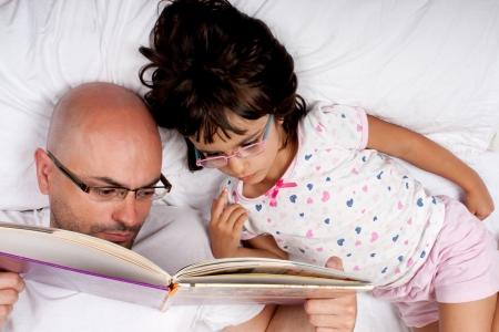 Vader en dochter met bril lezen van een boek in bed Stockfoto