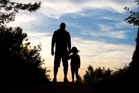 backlit: Silhouet van vader en dochter hand in hand te kijken naar de zonsondergang op de top van een bospad