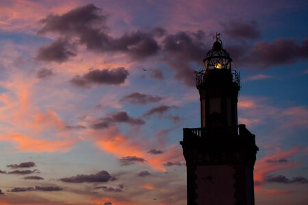 Silhouette of lighthouse at sunset in Fuenterraba, Basque Country photo
