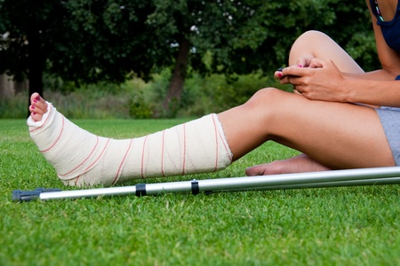 Leg in plaster of a girl sitting on the grass writing a text message with her smartphone. Crutches lying down at her side. Banque d'images