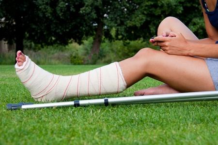 pierna rota: Pierna en yeso de una niña sentada en el césped escribir un mensaje de texto con su teléfono inteligente. Las muletas se acuesta a su lado.