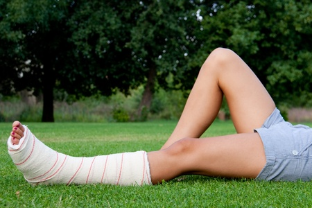 Leg in plaster of a girl lying on the grass resting
