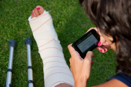 mishap: girl with a broken leg sitting in the grass using her smartphone to tell  friends the accident