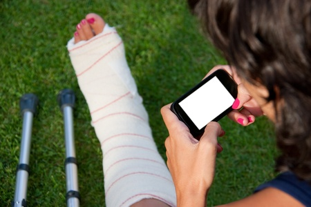 plaster foot: girl with a broken leg sitting in the grass using her smart phone with a blank screen