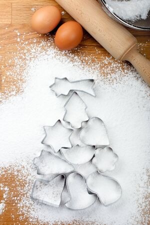 molds: Christmas tree made with cookie cutters on icing sugar snow, eggs, a roller, and a screen on a wooden table  Stock Photo