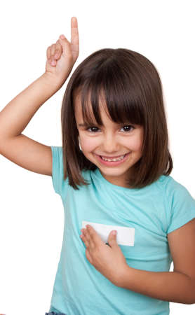 Smiling little girl lifting a finger and touching a white sticker attached to his shirt with the other hand.