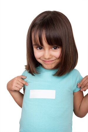 affixed: Smiling little girl pointing to white sticker affixed to her blue shirt. Copy space. Stock Photo