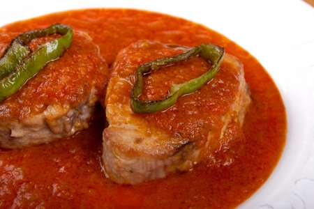 Tuna fish in tomato sauce with slices of fried pepper. Traditional basque cuisine.