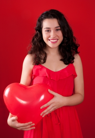 Happy and beautiful girl dressed in red holding a red heart shaped ballon  Red background  Stock Photo
