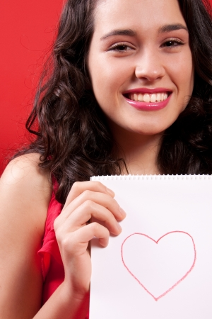 Happy and beautiful girl holding a notebook where is a drawing of a red heart, Red background. Stock Photo - 16613491
