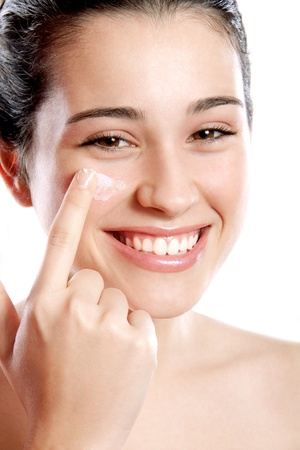 Beautiful and happy girl applying moisturizing cream on her cheek. Healthy smile. Isolated.