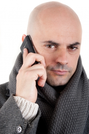 Bald man with tweed coat and scarf on the phone looking at camera  Isolated  photo