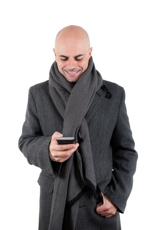 Bald man with tweed coat and scarf using his smart phone smiling  Isolated photo